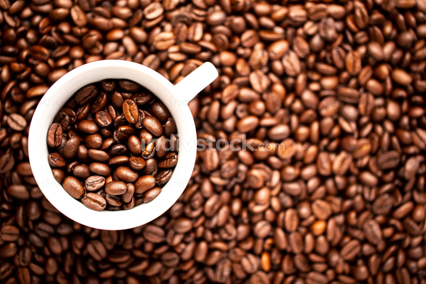 White cup with coffee beans on a background of coffee beans
