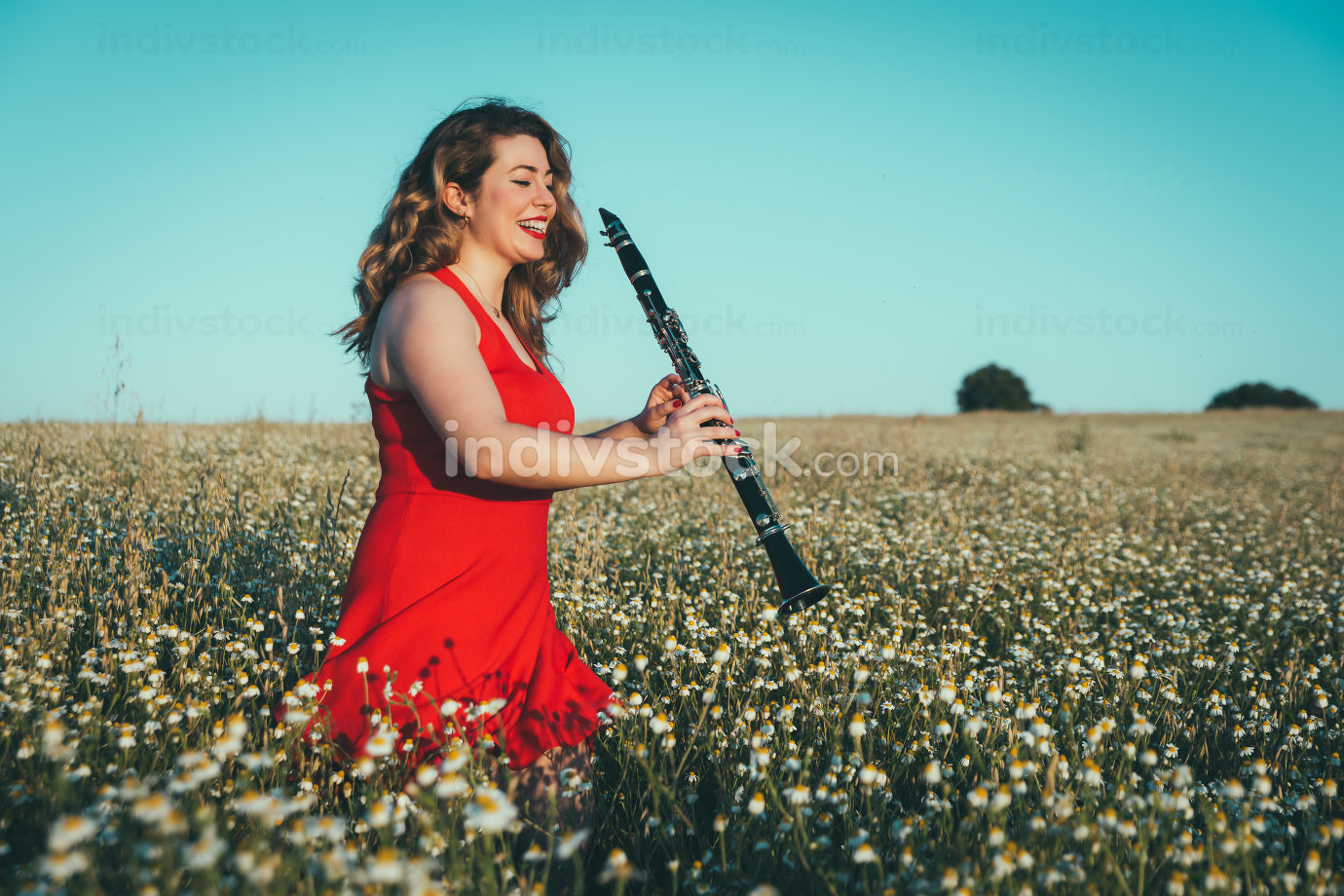woman in a red dress playing the clarinet in a field of daisies