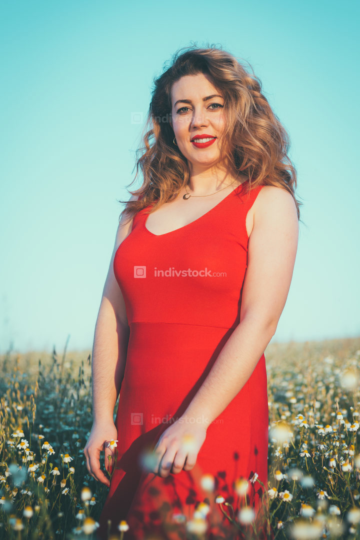 woman in red dress enjoying freedom in a field of daisies