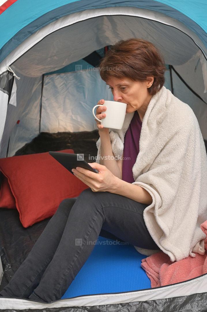 Woman sit inside a tent enjoying a cup of tea