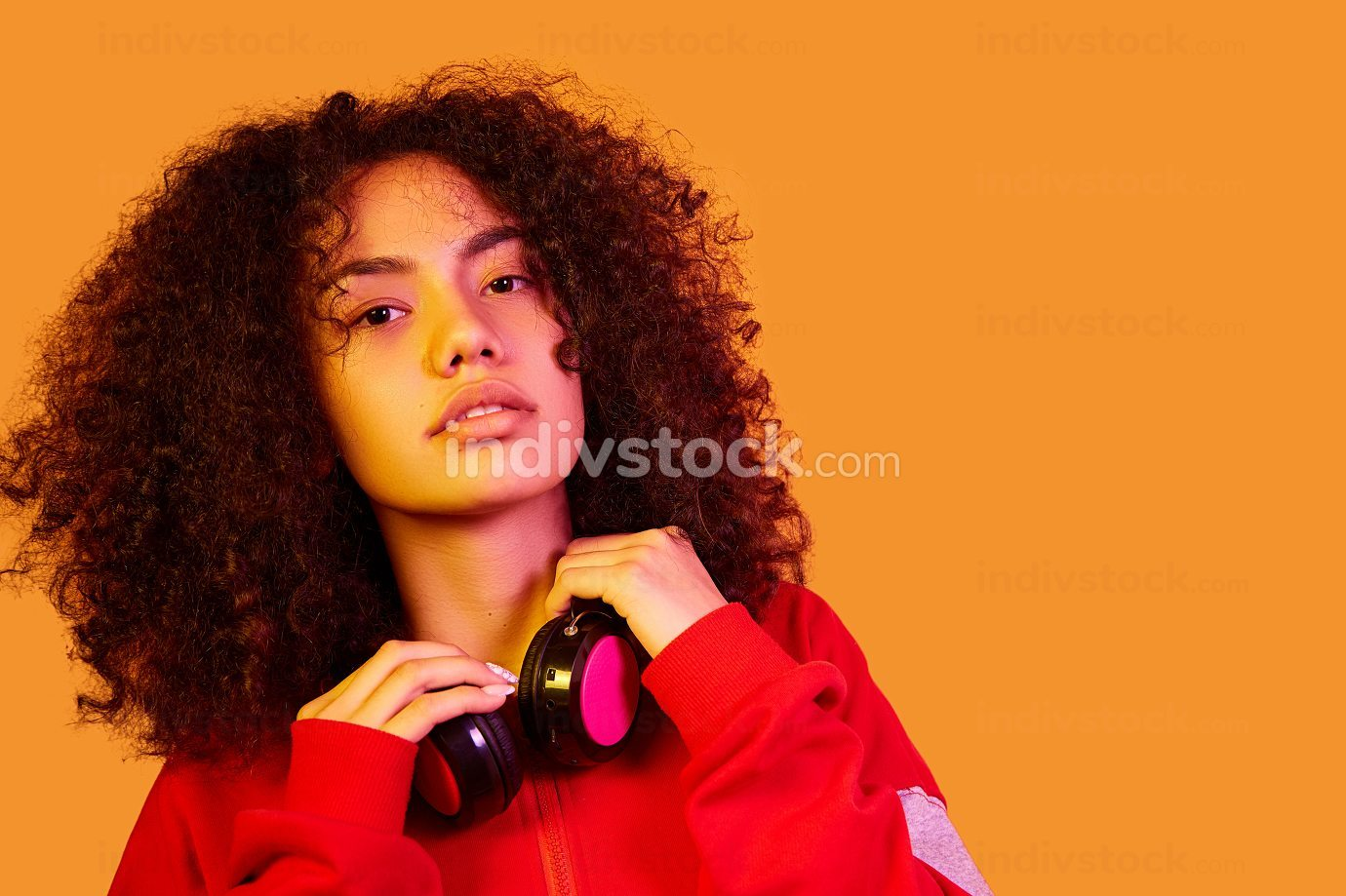 young beautiful African-American girl in a red hoodie on a yellow isolated background in yellow lighting