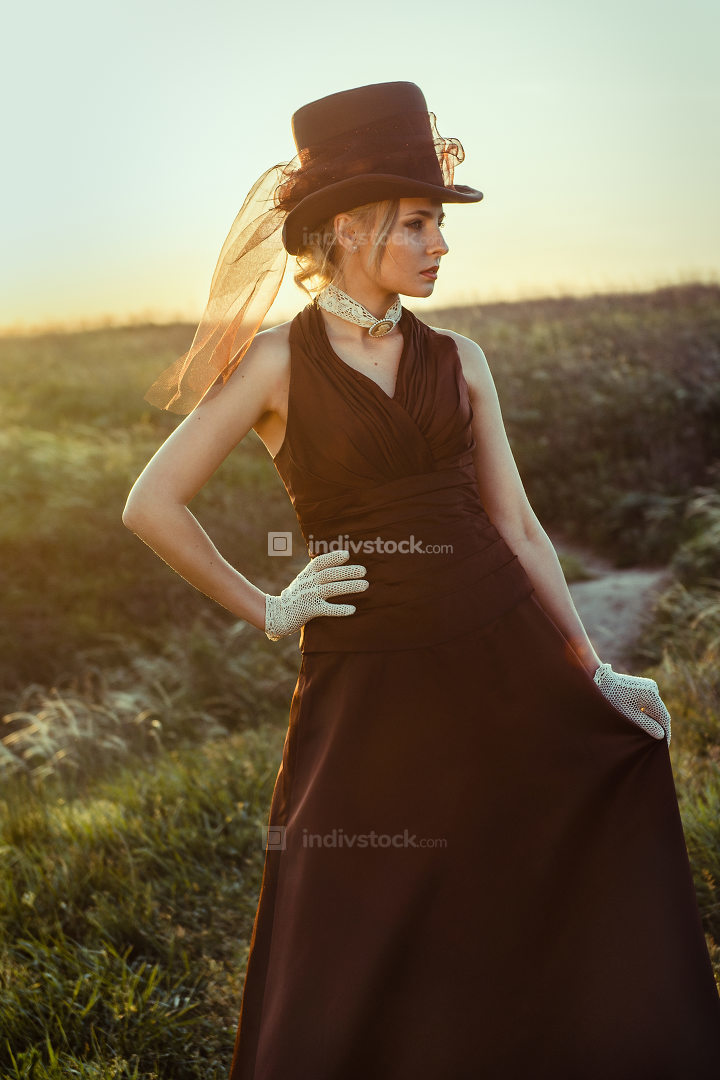 young blonde girl in a brown vintage dress and top hat