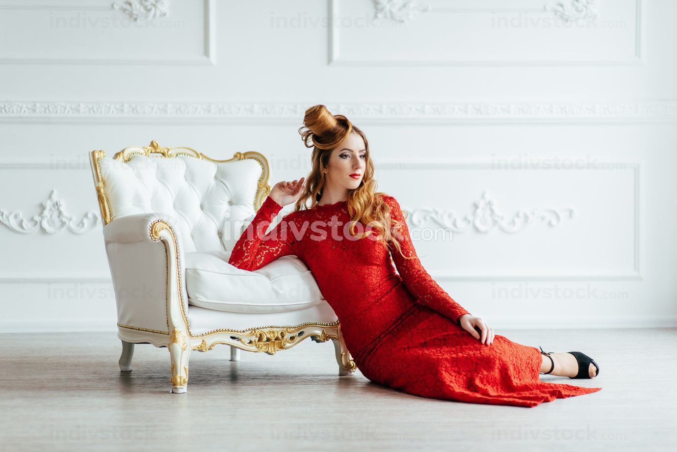 young girl with red hair in a bright red dress in a bright room