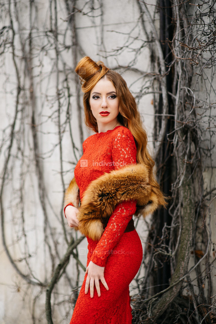young girl with red hair in a bright red dress near a tree