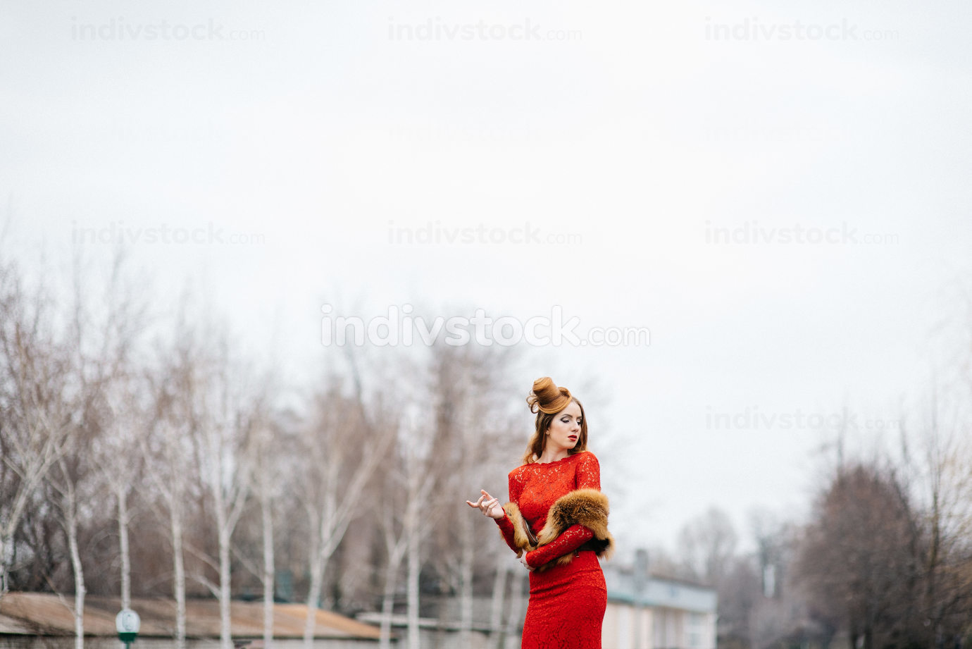 young girl with red hair in a bright red dress on the railway tr