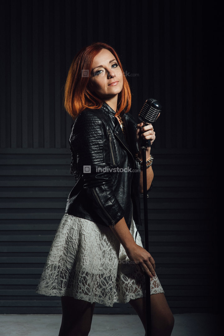 young red-haired girl in a white dress and a black leather rocke