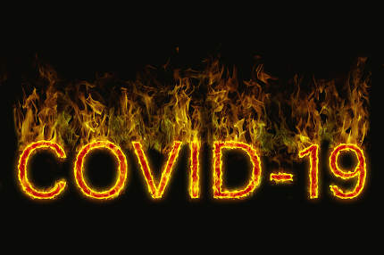 A designation of a Covid 19 virus as burning letters on a black background