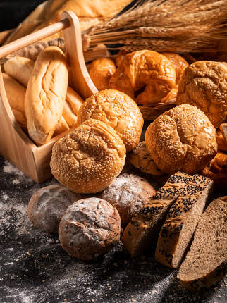 a group of bread on the black wooden table with sunlight