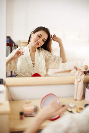 a young beautiful Asian woman in a beige lace dressing gown put on morning makeup and does her hair . shallow depth of focus. selective focus