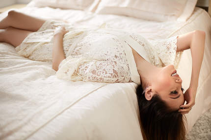 a young beautiful girl in a beige lace nightgown is lying on her back on a light bed