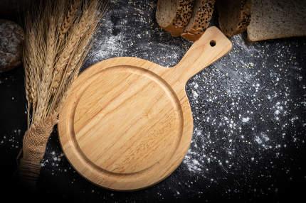 An empty wooden cutting board and wheat on the table with bread