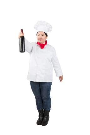 Attractive young chef or waiter holding champagne bottle