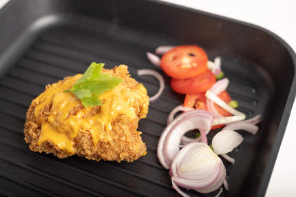 Chicken fried topped cheese in a black pan