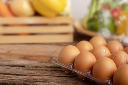 Eggs in the plastic on the wooden table