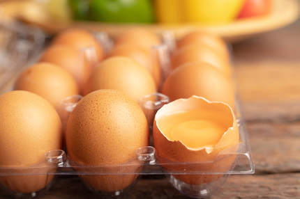 eggs of chicken and yolk with broken in plastic box on the woode