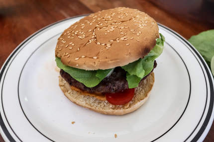 Homemade making of a grilled burger with tomatoes and salad on a
