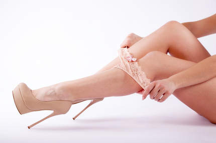 Legs of a woman in high heels and with a tanga slip