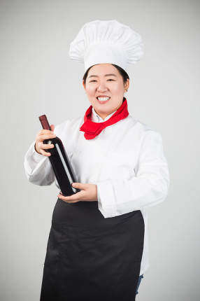 Attractive young chef or waiter holding green champagne bottle isolated in white