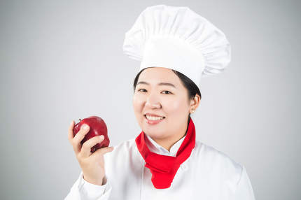 cooking and food concept - smiling female chef, holding a Red Delicious