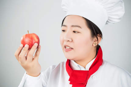 cooking and food concept - smiling female chef, holding a red apple