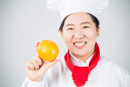 cooking and food concept - smiling female chef, holding orange
