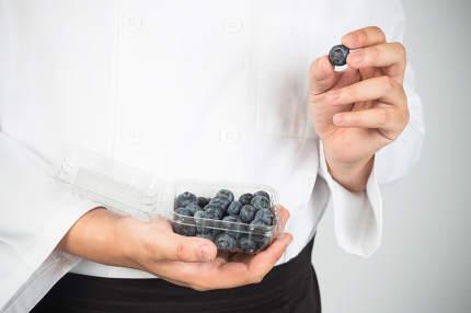 Hand holding blueberry, isolated on white background.