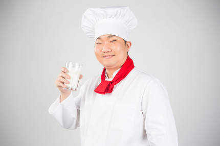 chef holding glass cup and drink yogurt or milk nice photo