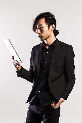 Serious young male executive using digital tablet against gray background