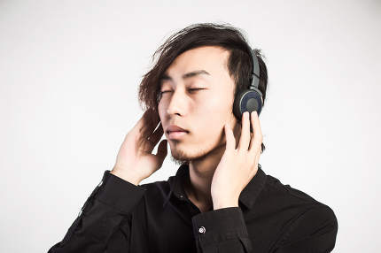 Handsome young man putting on headphones
