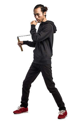 asian man in a hood is using a nunchaku isolated on white