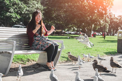 Girl sits on a chair play with seagull nice shot