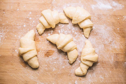 Tasty croissants with spikelets on background