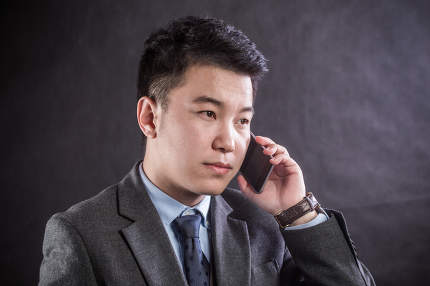 Close up of a young man leaning against a grey wall using mobile phone. Portrait of a happy business man holding a smartphone. Man in casual typing and reading a message on cell phone with copyspace.