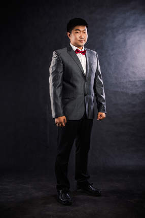 Photo of stylish man in elegant black suit studio shot