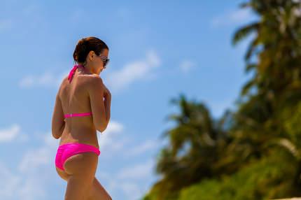 Maldives, a woman in a bikini walking along the beach