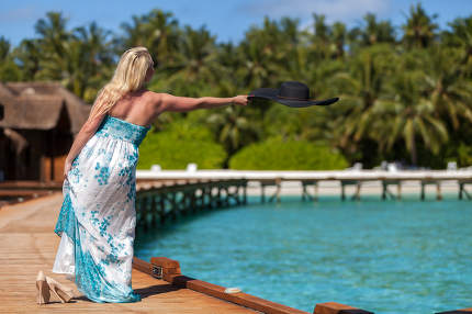 Maldives, Woman throwing her hat into the water