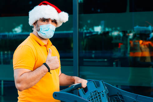 mature man with medical mask and christmas hat shopping