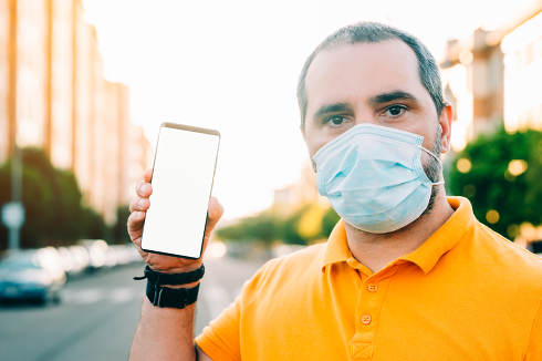 Portrait of 40s aged man with surgical medical mask standing, holding and showing smart phone display.