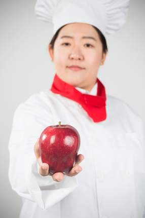 smiling female chef, holding a Red Delicious