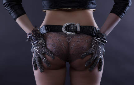 the bottom of a woman in panties with a belt and gloves