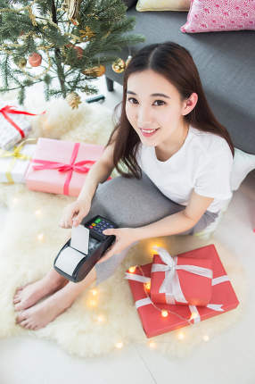 woman use payment terminal for shopping in Christmas