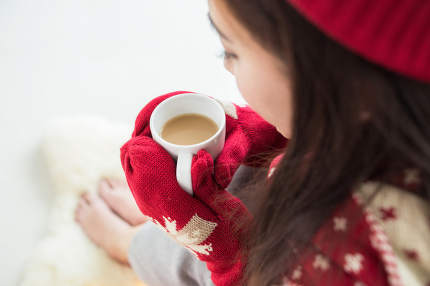 Woman with cup of coffee in hands in christmas,
