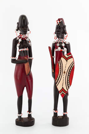 Wooden figure of a couple of maasai on white background