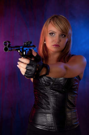 Young blonde woman in leather and with a gun