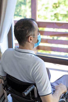 young man wearing face mask sitting in a wheelchair alone lookin