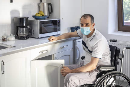 Young man wearing face mask sitting in front of kitchen