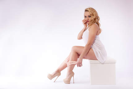 Young woman sitting on a stool in white top, high-heels and ling