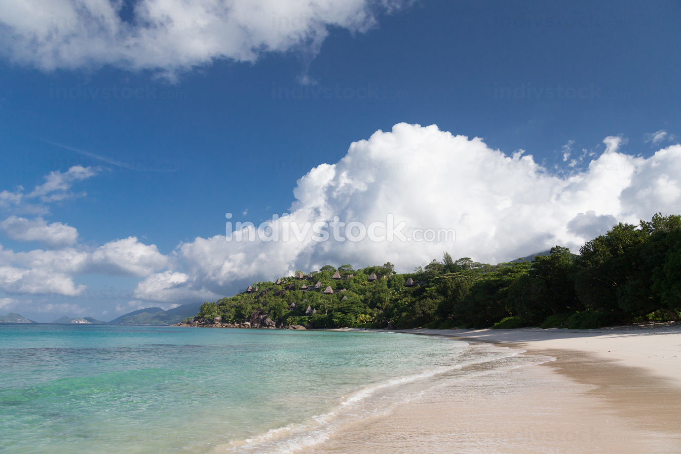 A beach on the Seychelles island with white sand and stones