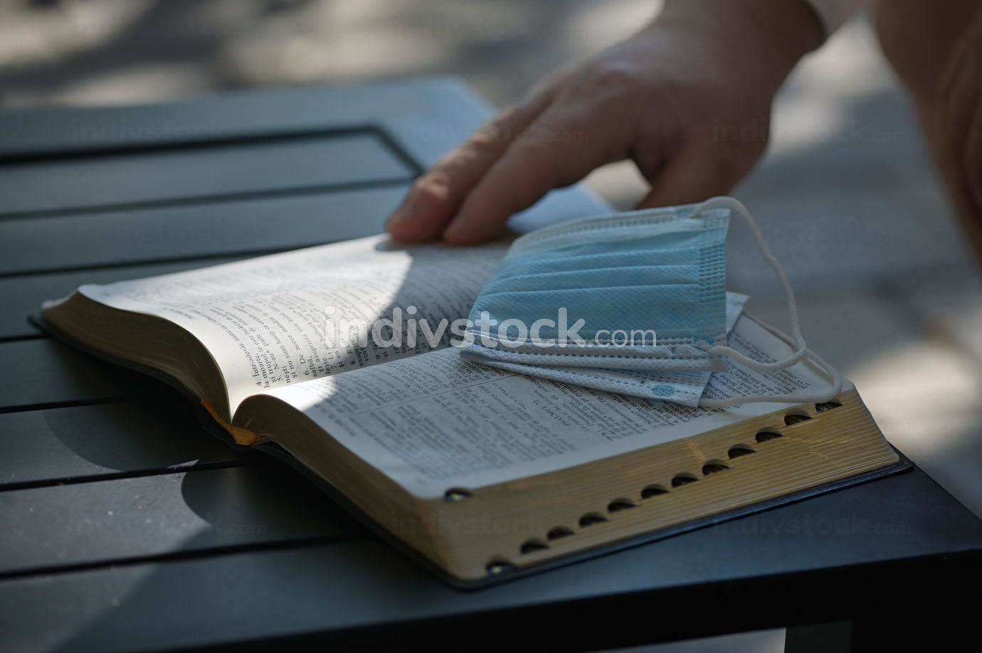 A Medical Respiratory Mask On Holy Bible at Sunset