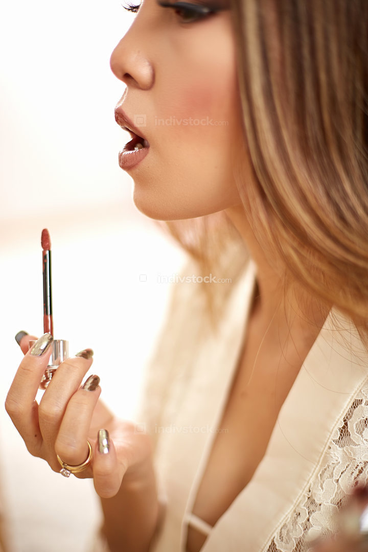 a young beautiful Asian woman in a beige lace dressing gown put on morning makeup and puts lipstick on her lips. in the bedroom . shallow depth of focus. selective focus